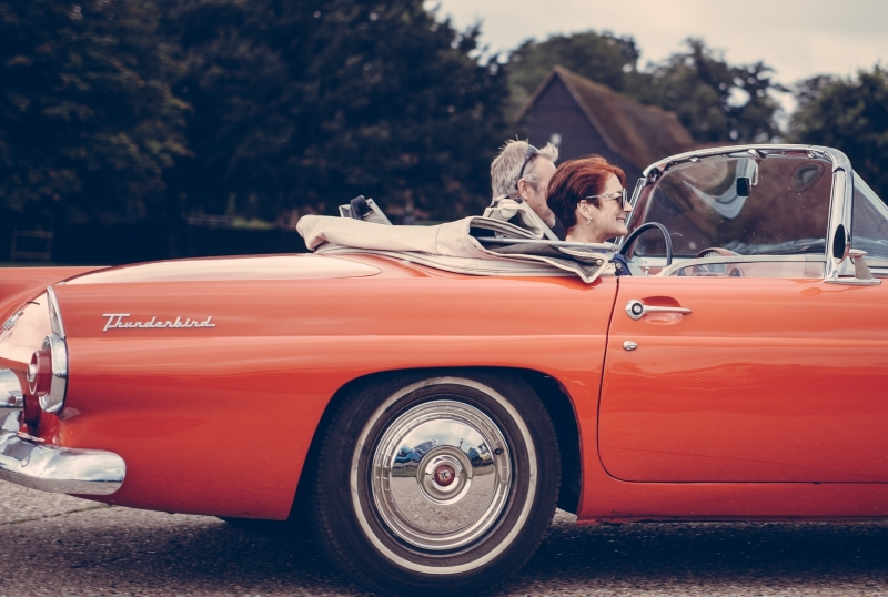 Mann und Frau mit Brille in rotem Ford Thunderbird